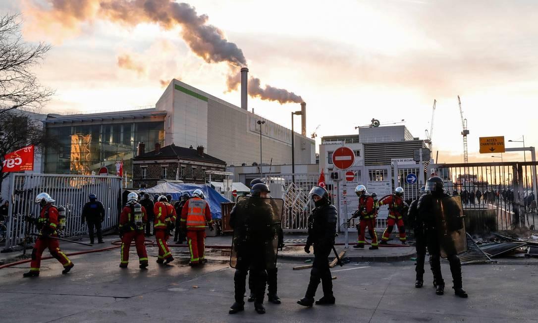 Policiais e bombeiros intervêm no local após o bloqueio do incinerador de resíduos em Ivry-sur-Seine, nos arredores de Paris, nesta quarta-feira. A frança enfrente o 42º dia de uma greve geral contra a reforma da previdência Foto: Thomas Samson / AFP