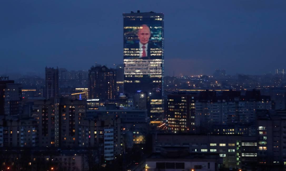 Telão instalada em prédio comercial de São Petersburgo mostra imagem do presidente Vladimir Putin, durante o discurso desta quarta-feira Foto: ANTON VAGANOV / REUTERS