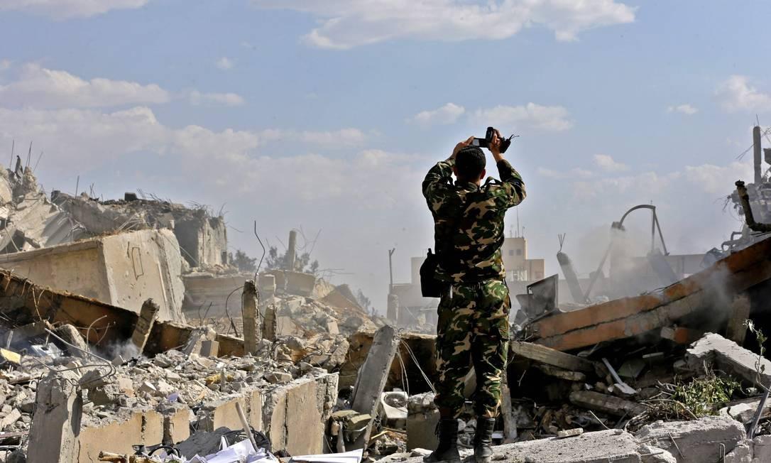 Soldado sírio inspeciona destroços do Centro de Pesquisa e Estudos Científicos em Barzeh, ao Norte de Damasco Foto: LOUAI BESHARA / AFP/14-04-2018