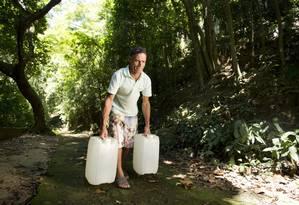 Vardecino de Oliveira carrega 40 litros de água por uma área de mata Foto: Márcia Foletto / Agência O Globo