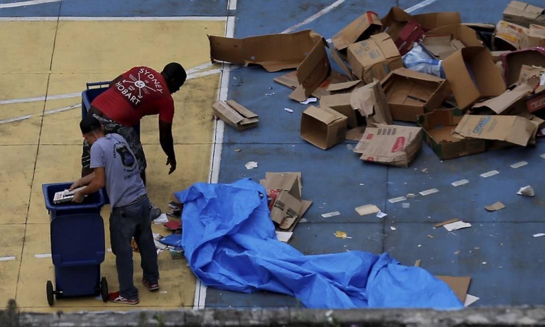 Livros jogados pela janela e recolhidos por uma cooperativa Foto: MARCELO THEOBALD / Agência O Globo