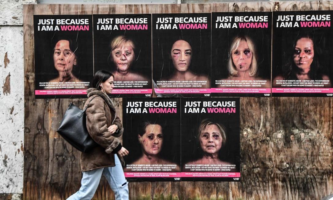 """Mulher passa por cartazes da campanha """"Só porque eu sou uma mulher"""". Nessa série, mulheres protagonistas da política mundial são retratadas como vítimas de violência de gênero Foto: Miguel Medina / AFP"""
