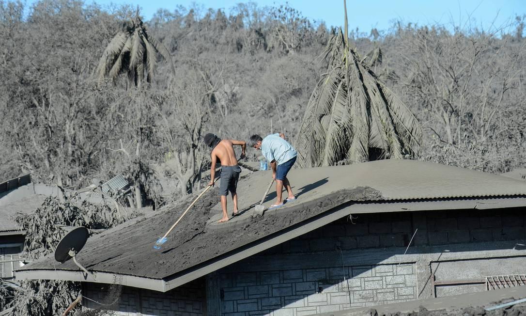 Moradores limpam o telhado de sua casa coberta de lama e cinzas devido à erupção do vulcão Taal nas proximidades em uma vila em Laurel, província de Batangas, Filipinas Foto: Ted Aljibe / AFP