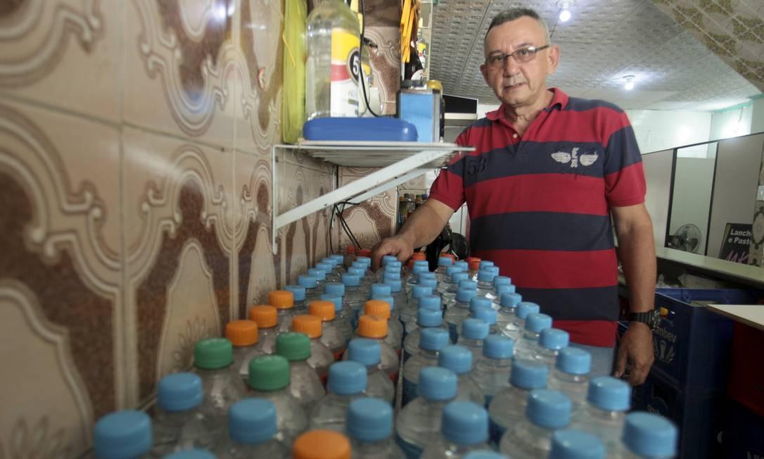 O comerciante Francisco Leitão, dono de um bar na Avenida Itaoca, em Bonsucesso, precisou aumentar o estoque de água Foto: Gabriel de Paiva / Agência O Globo / 14-01-2020