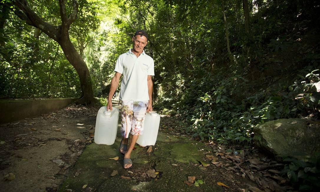 O servente Vardecino de Oliveira sai do Morro dos Prazeres para buscar a água da fonte centenária do Silvestre, na Floresta da Tijuca, duas vezes na semana, com dois galões de 20 litros Foto: Márcia Foletto / Agência O Globo