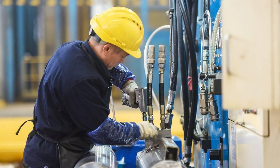 Operário trabalha em uma linha de produção de cilindros em uma fábrica em Hangzhou, na província de Zhejiang, leste da China Foto: STR / AFP