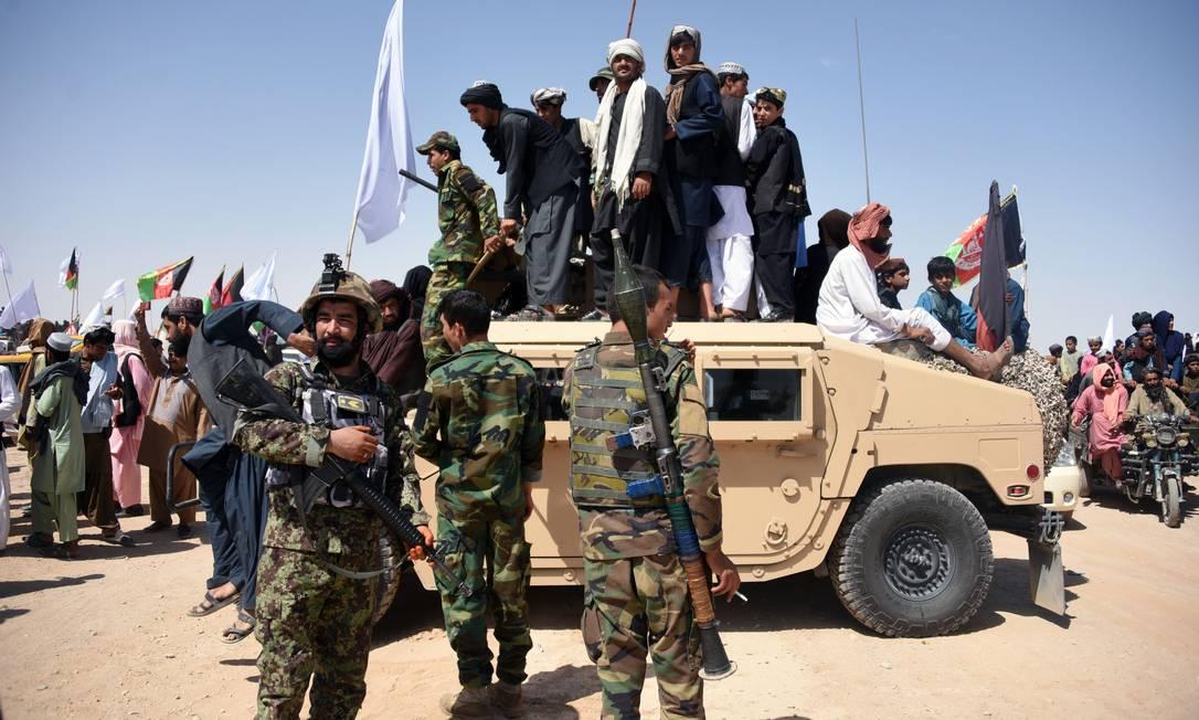 Militates do Talibã afegão e civis sobem em veículo blindado do Exército Nacional Afegão, na província de Kandahar, no Sul do Afeganistão Foto: JAVED TANVEER / AFP/17-06-2018