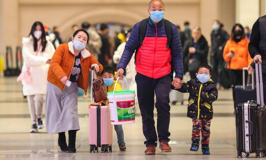 Pessoas usam máscaras enquanto caminham na estação ferroviária de Hankou, na província central de Hubei, na China. Os países asiáticos intensificaram as medidas para bloquear a propagação do coronavírus Foto: - / AFP