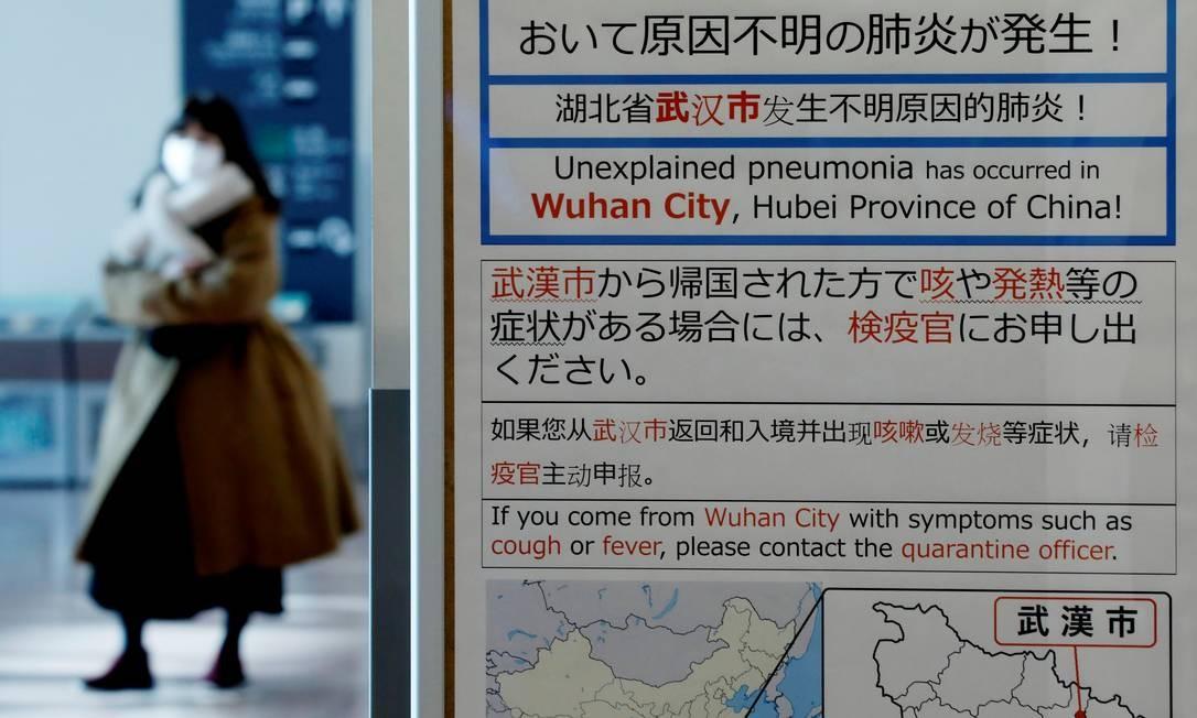 Uma mulher vestindo uma máscara passa por um aviso de quarentena sobre o surto de coronavírus, no saguão de chegada do aeroporto de Haneda em Tóquio, Japão Foto: KIM KYUNG-HOON / REUTERS