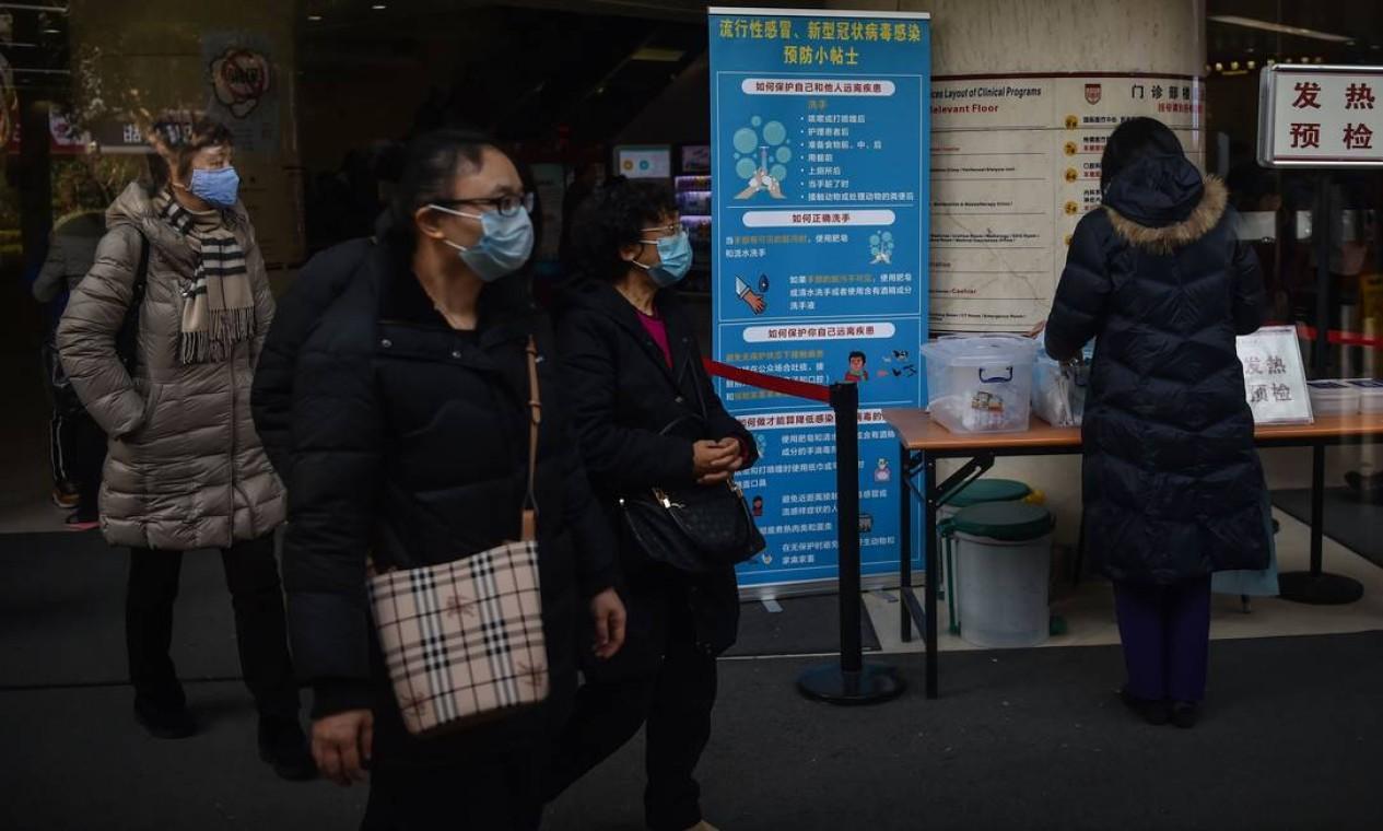 Pessoas caminham ao lado de uma sinalização detalhando práticas higiênicas para impedir a propagação do coronavírus, em Xangai Foto: HECTOR RETAMAL / AFP