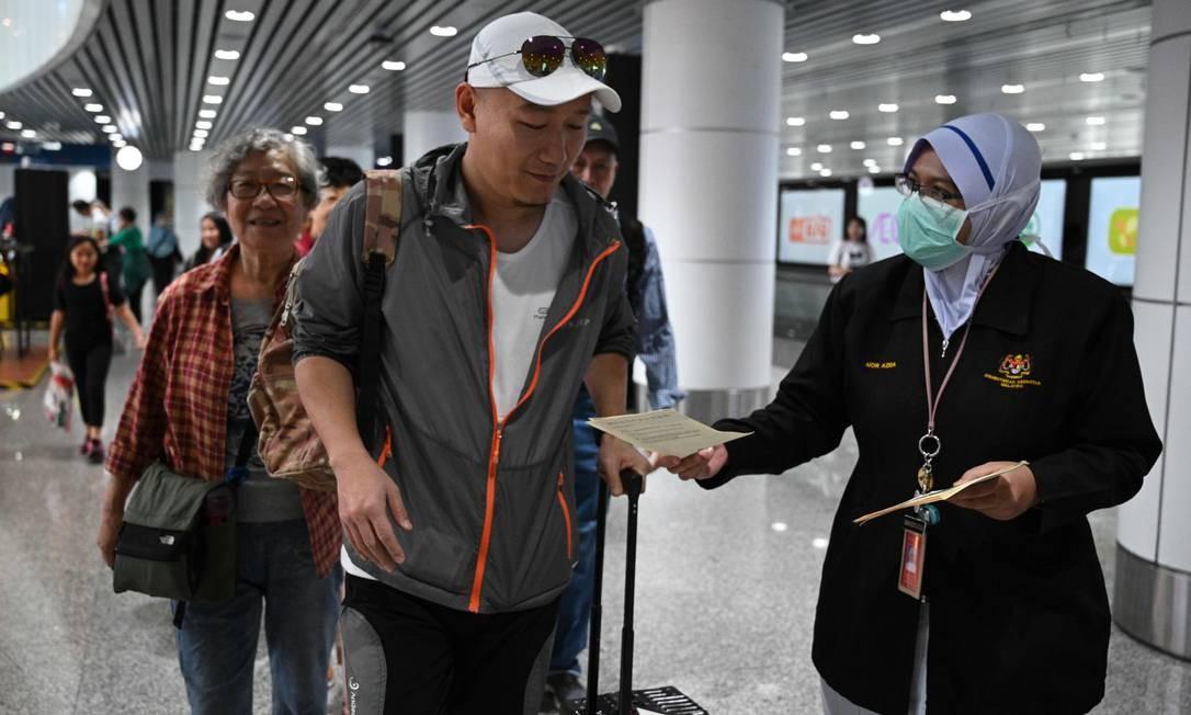 Oficial de saúde da Malásia entrega folhetos a passageiros que chegam no aeroporto internacional de Kuala Lumpur, em Sepang Foto: MOHD RASFAN / AFP