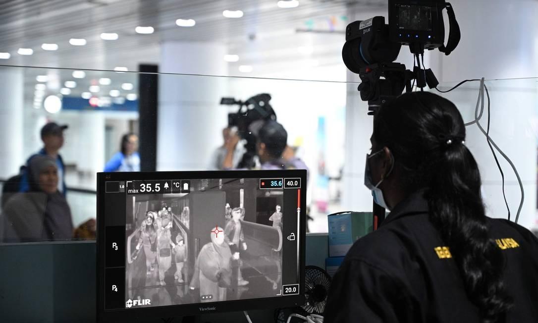 Oficial de saúde da Malásia rastreia passageiros que chegam com um scanner térmico no Aeroporto Internacional de Kuala Lumpur, em Sepang. Autoridades aeroportuárias do mundo todo temem uma pandemia internacional e intensificam a triagem de viajantes da China Foto: MOHD RASFAN / AFP