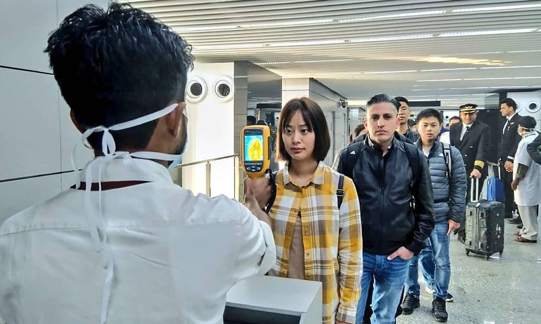 Foto divulgada pelo Ministério da Aviação Civil mostra um homem utilizando uma câmera termográfica para rastrear passageiros que chegam da Índia e da China no Aeroporto Internacional Netaji Subhash Chandra Bose, em Calcutá. Os países asiáticos intensificaram as medidas para bloquear a propagação do novo vírus Foto: HANDOUT / AFP