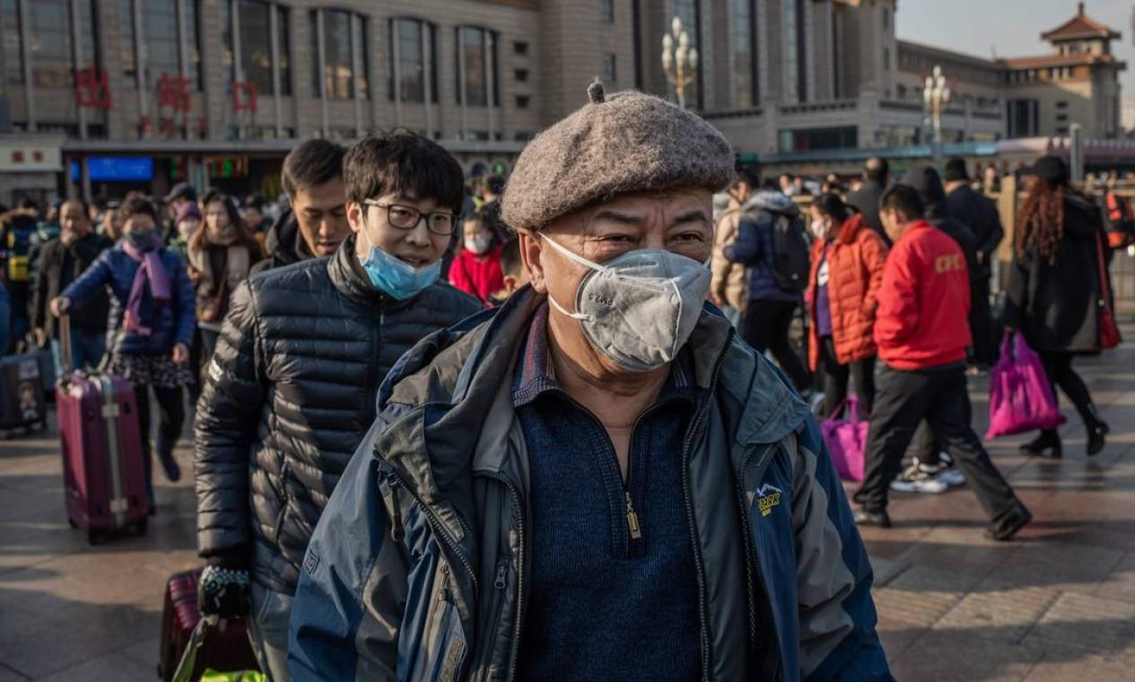 Pessoas usam máscaras protetoras enquanto chegam à estação ferroviária de Pequim para voltar para o Ano Novo Lunar. A China confirmou a transmissão do coronavírus de humano para humano Foto: NICOLAS ASFOURI / AFP