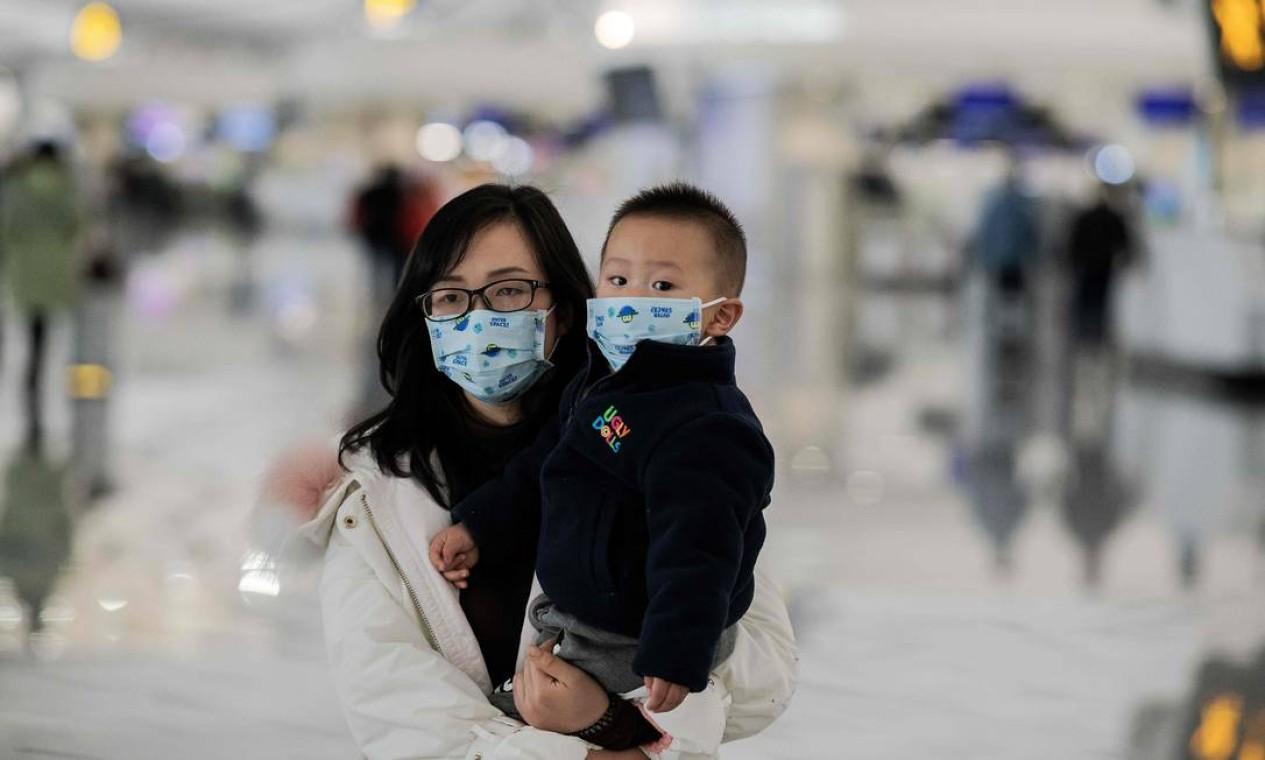 Uma mulher com uma criança no colo usa máscaras de proteção no aeroporto internacional de Daxing, em Pequim. Número de mortes causadas pelo coronavírus na China chegou a 26 nesta sexta-feira Foto: NICOLAS ASFOURI / AFP
