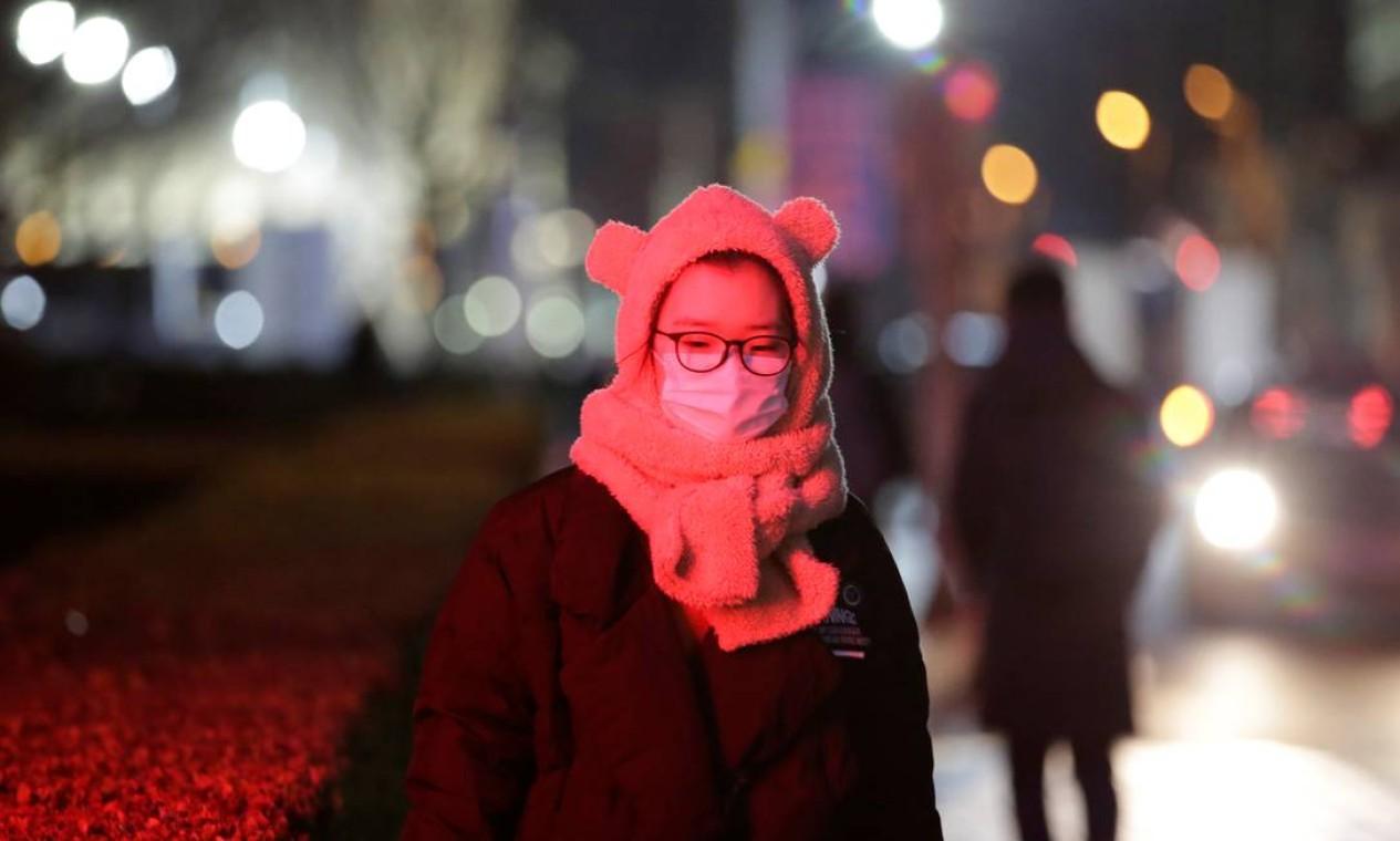 Uma mulher usa máscara enquanto caminha ao longo de uma rua em Pequim, na China Foto: JASON LEE / REUTERS