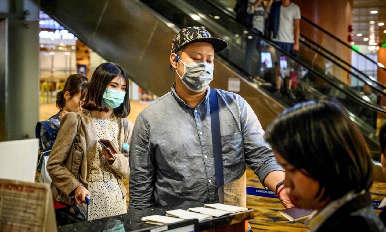 Passageiros com máscaras embarcam no Aeroporto Internacional de Yangon, em Myanmar Foto: MLADEN ANTONOV / AFP