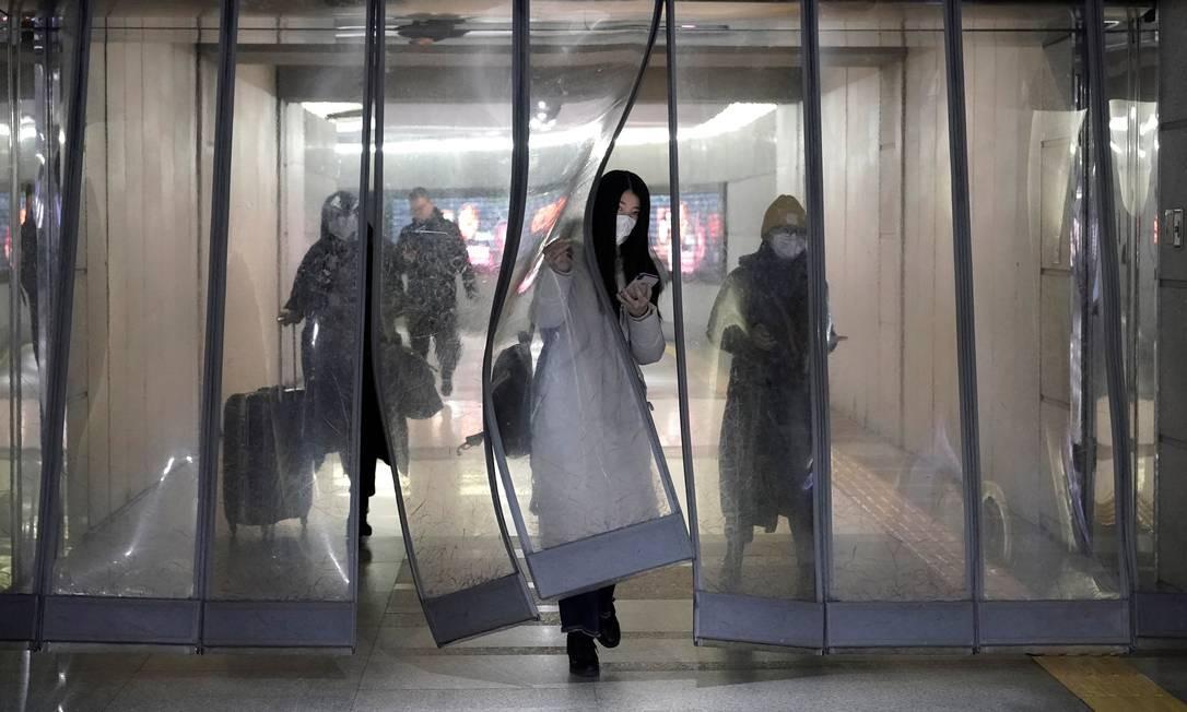 Pessoas com máscaras passam por passagem subterrânea para o metrô em Pequim Foto: JASON LEE / REUTERS