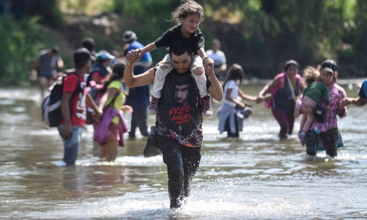 Imigrantes da América Central, principalmente hondurenhos, atravessam em caravana o rio Suichate, fronteira natural entre Tecum Uman, na Guatemala, e Ciudad Hidalgo, no México, na tentativa de chegar aos EUA Foto: JOHAN ORDONEZ / AFP