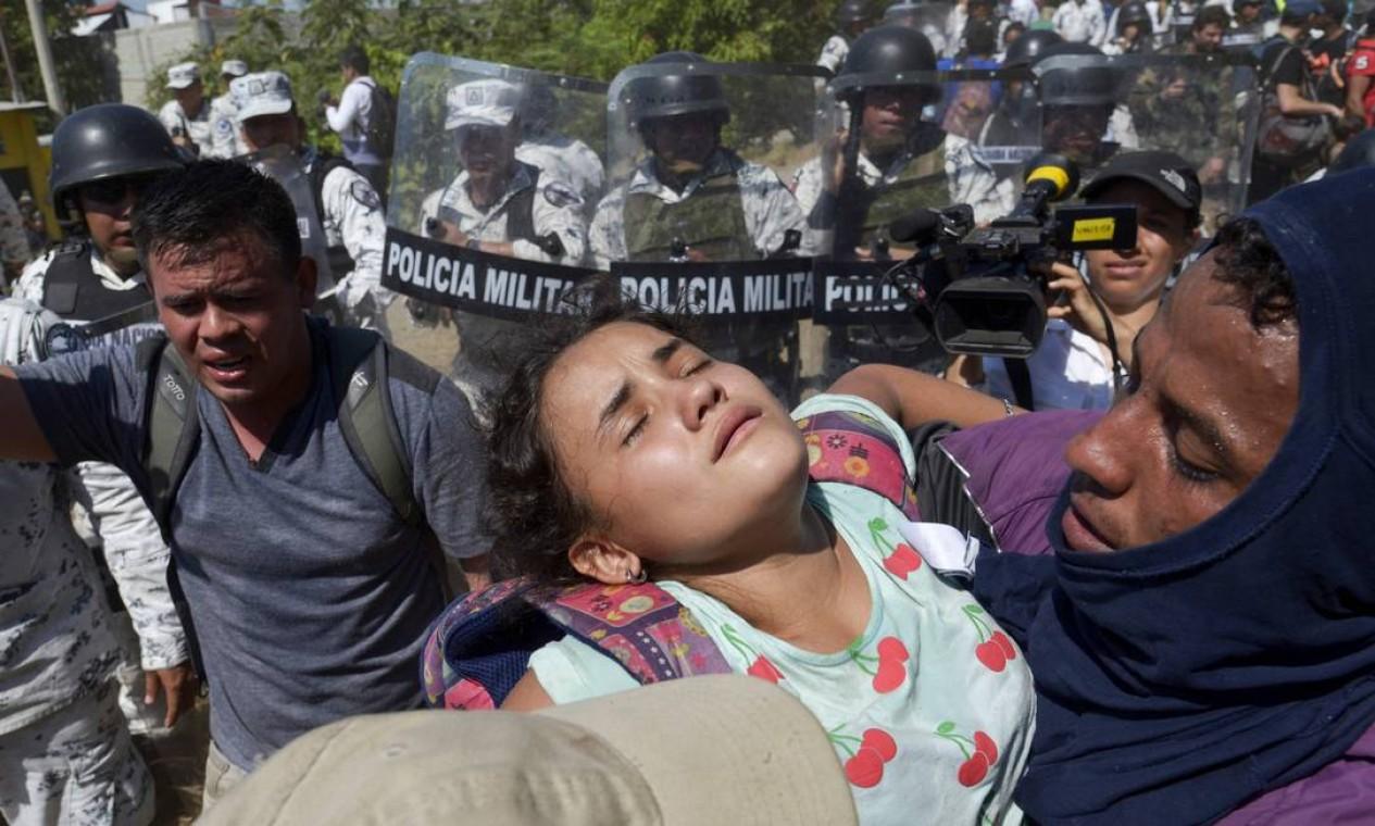 Homem carrega uma garota depois que as forças de segurança mexicanas os impedem de atravessar ilegalmente para o México em Ciudad Hidalgo Foto: ISAAC GUZMAN / AFP