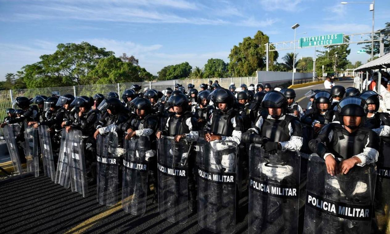 Forças armadas mexicanas montam guarda na ponte internacional que liga a Guatemala ao México enquanto imigrantes da América Central viajam em caravana para os EUA. A maioria dos migrantes saiu na terça-feira passada de Honduras e chegou na manhã de sábado à ponte sobre o rio Suchiate Foto: JOHAN ORDONEZ / AFP