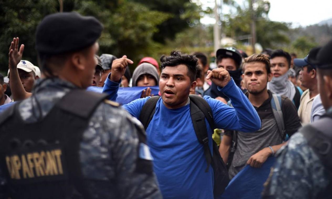 Imigrantes hondurenhos discutem com policiais guatemaltecos depois de passarem por uma cerca policial na passagem da fronteira entre Honduras e Guatemala, em 16 de janeiro Foto: JOHAN ORDONEZ / AFP