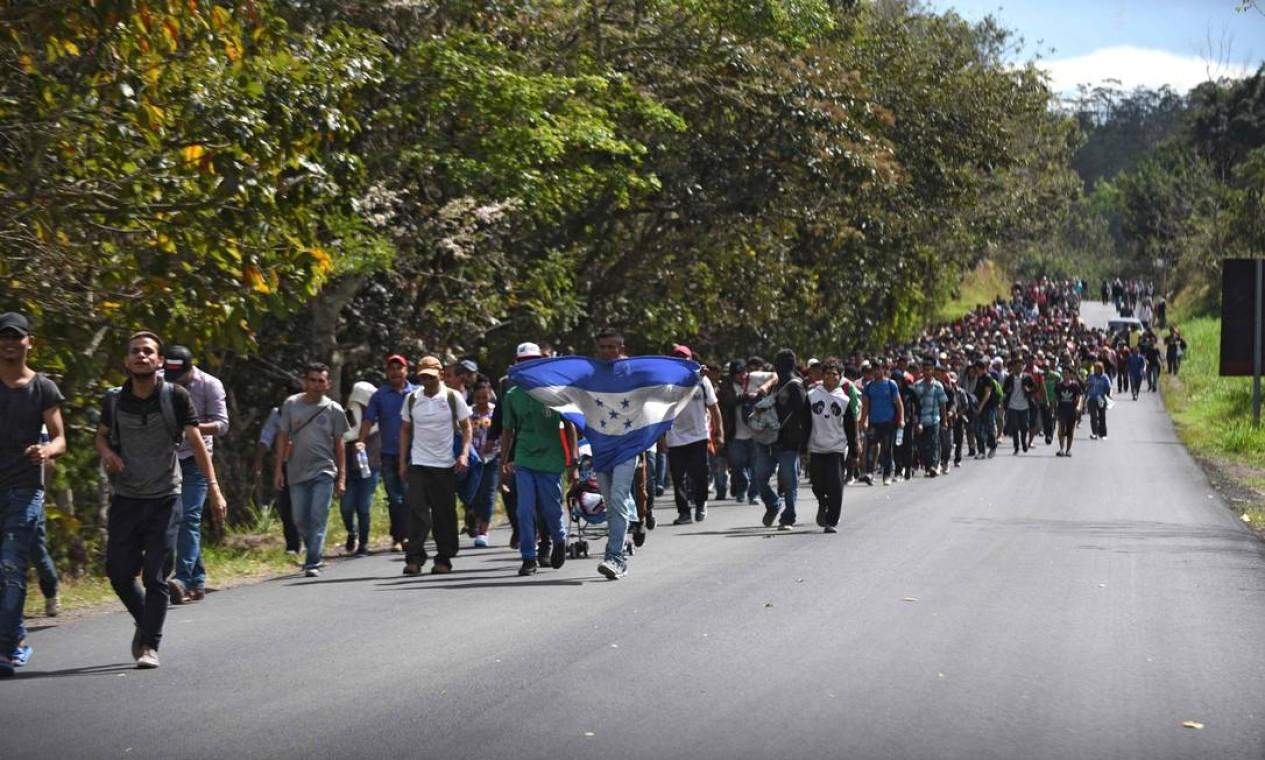 Os imigrantes hondurenhos caminham com uma bandeira do país perto de Esquipulas, na Guatemala, em 16 de janeiro, depois de cruzar a fronteira em Agua Caliente, Honduras, a caminho dos EUA. Caravana, que se formou em Honduras, está percorrendo a Guatemala e tem cerca de 3 mil pessoas Foto: JOHAN ORDONEZ / AFP