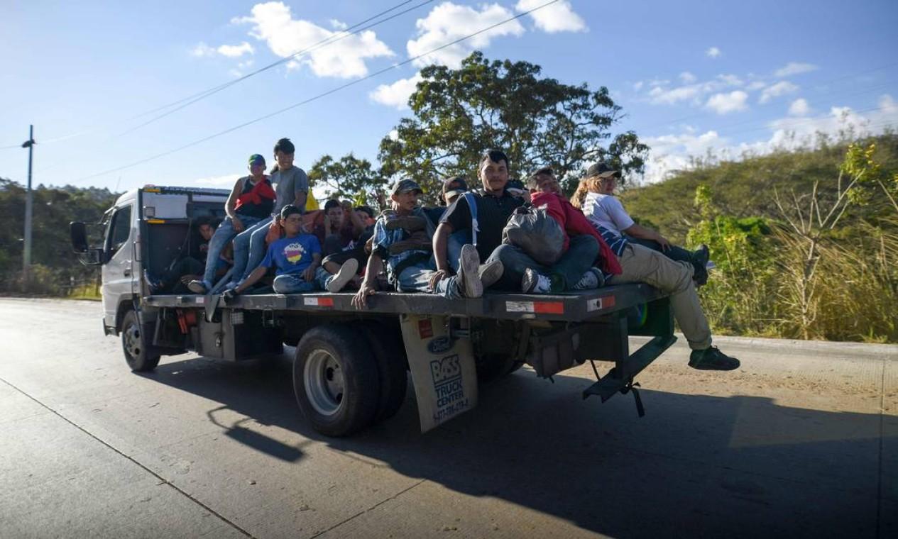 Imigrantes hondurenhos viajam na traseira de um caminhão no departamento de Zacapa, Guatemala, em 17 de janeiro, a caminho dos EUA. - O presidente mexicano Andres Manuel Lopez Obrador ofereceu 4 mil empregos na a migrantes em uma nova caravana que atualmente cruza a América Central em direção ao país norte-americano Foto: JOHAN ORDONEZ / AFP