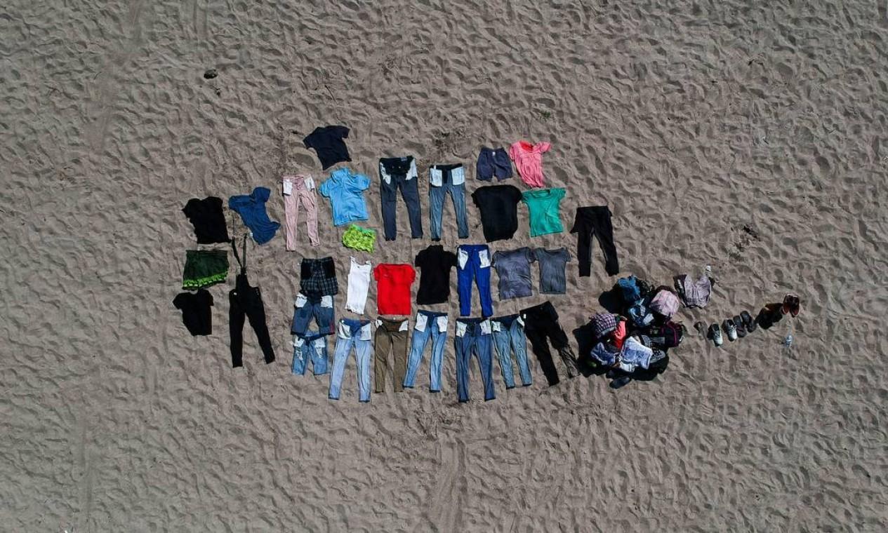 Peças de roupas de imigrantes secam ao sol às margens do rio Suchiate Foto: CARLOS ALONZO / AFP