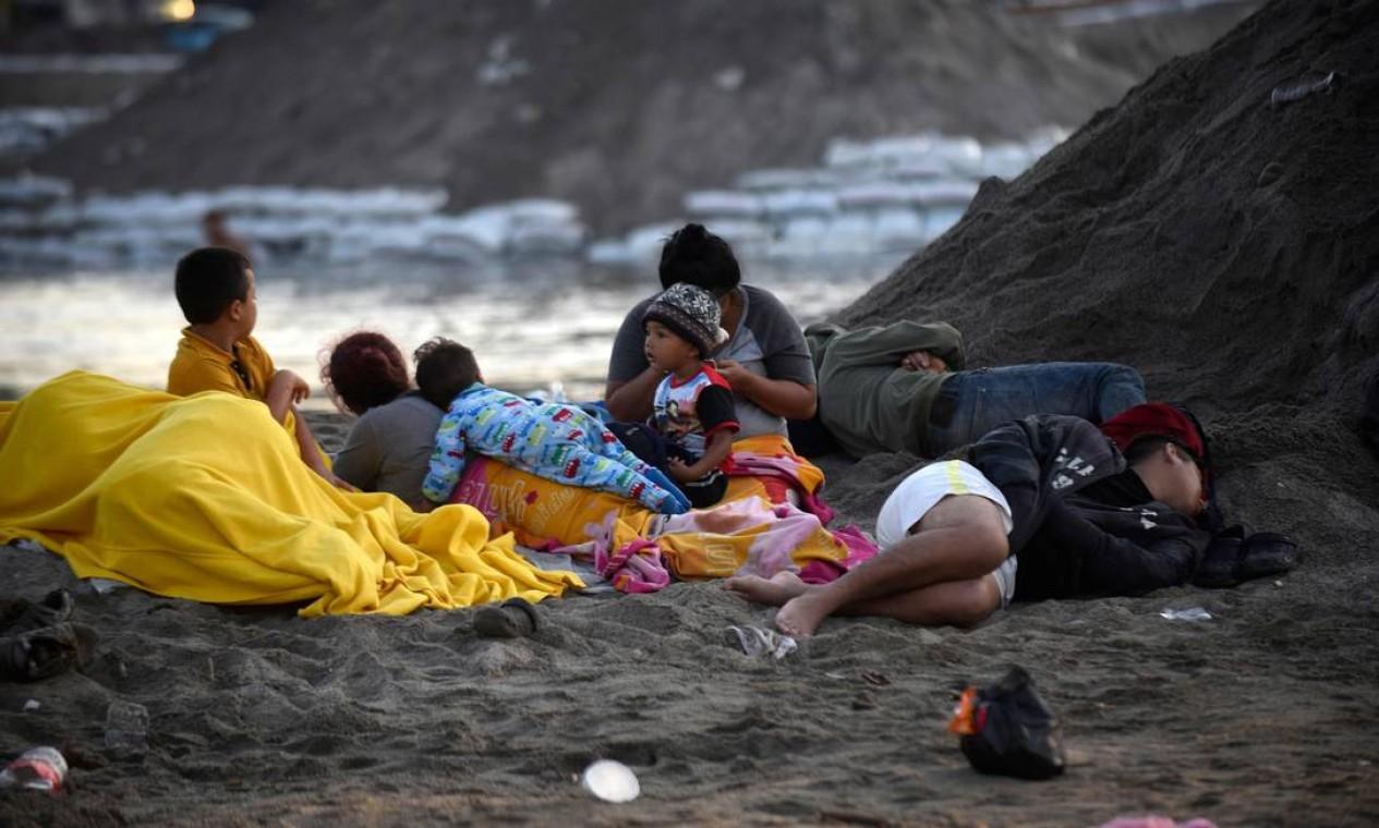Imigrantes na margem do rio Suichate, onde passaram a noite, em Ciudad Hidalgo, no México, depois de atravessar de Tecum Uman, na Guatemala, nesta terça-feira Foto: JOHAN ORDONEZ / AFP