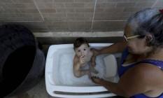 Logo nos primeiros dias em que o problema começou a aparecer, dona Vera Lúcia passou a dar banho em sua netinha, Laura, com água armazenada da chuva Foto: Marcelo Theobald em 7/1/2020 / Agência O Globo
