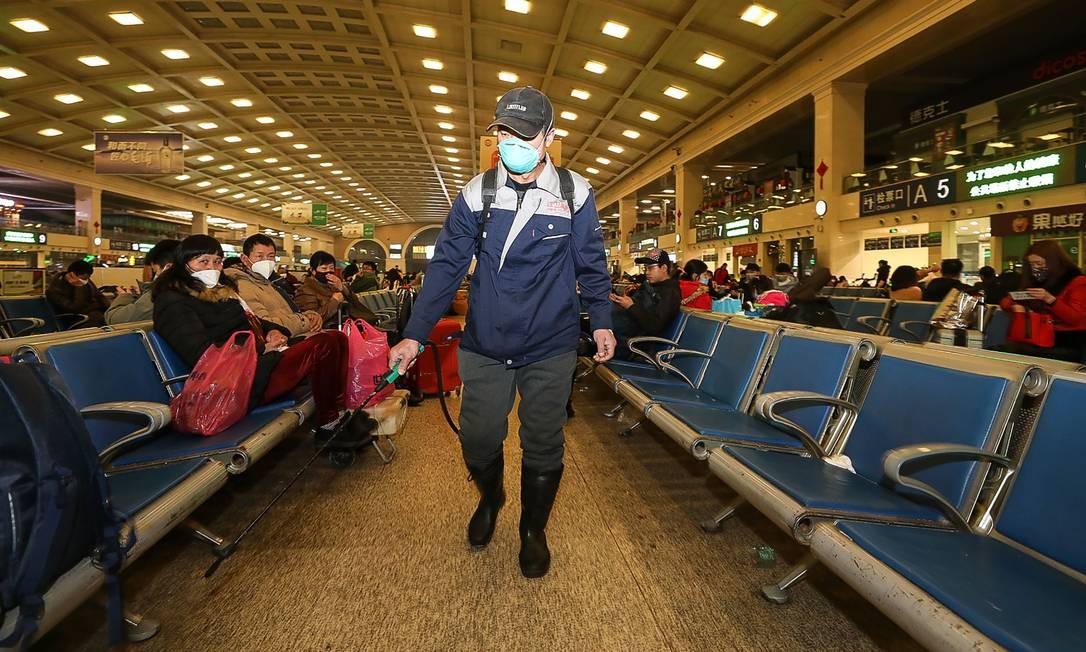 Estação de trem em Wuhan, na China, é desinfetada por funcionário em meio ao temor da disseminação do coronavírus pelo mundo Foto: STR / AFP