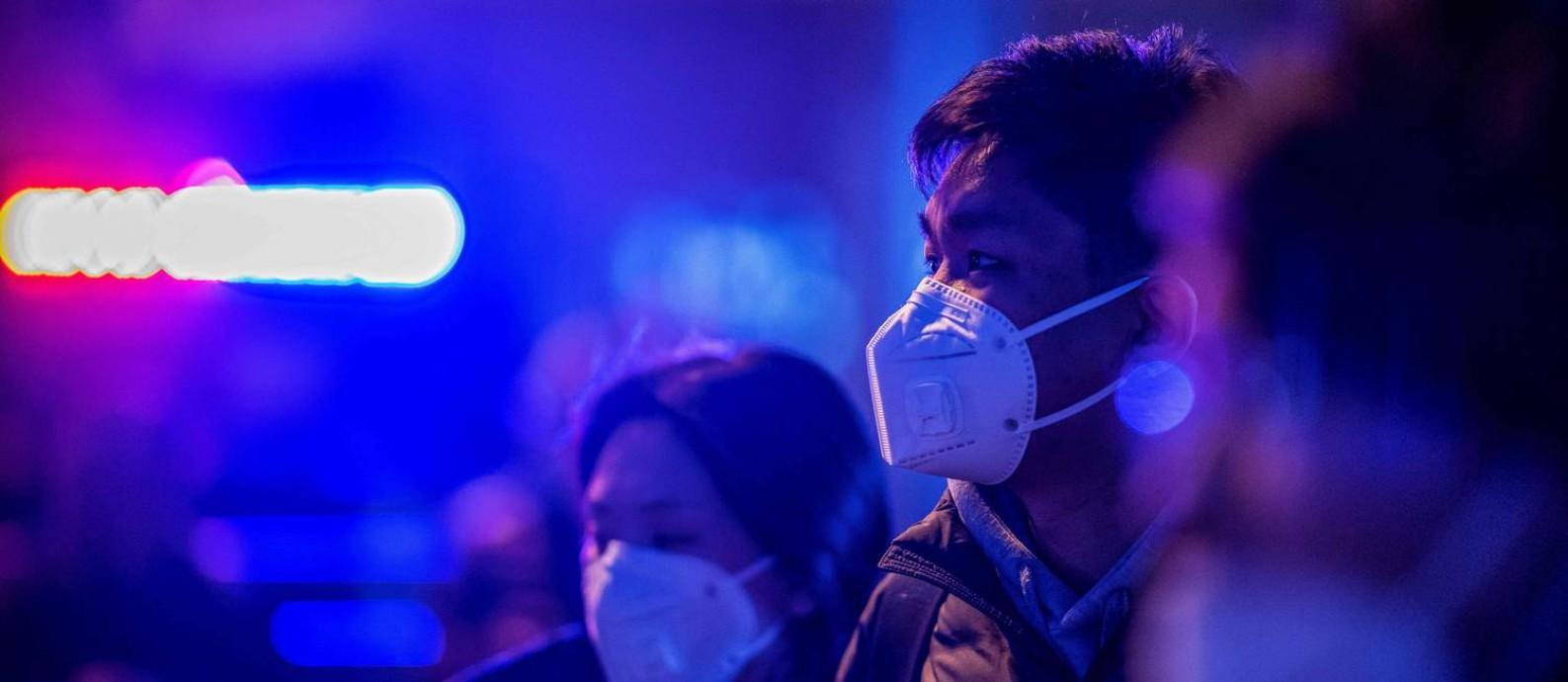 Pedestres usam máscaras de proteção do lado de fora da estação de trem de Pequim nesta quarta-feira (22) Foto: NICOLAS ASFOURI / AFP