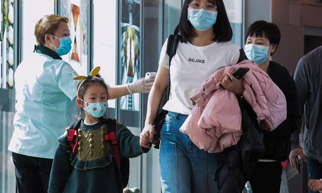 Funcionária vistoria passageiros que chegam da China no Aeroporto Internacional de Changi, em Cingapura Foto: ROSLAN RAHMAN/AFP