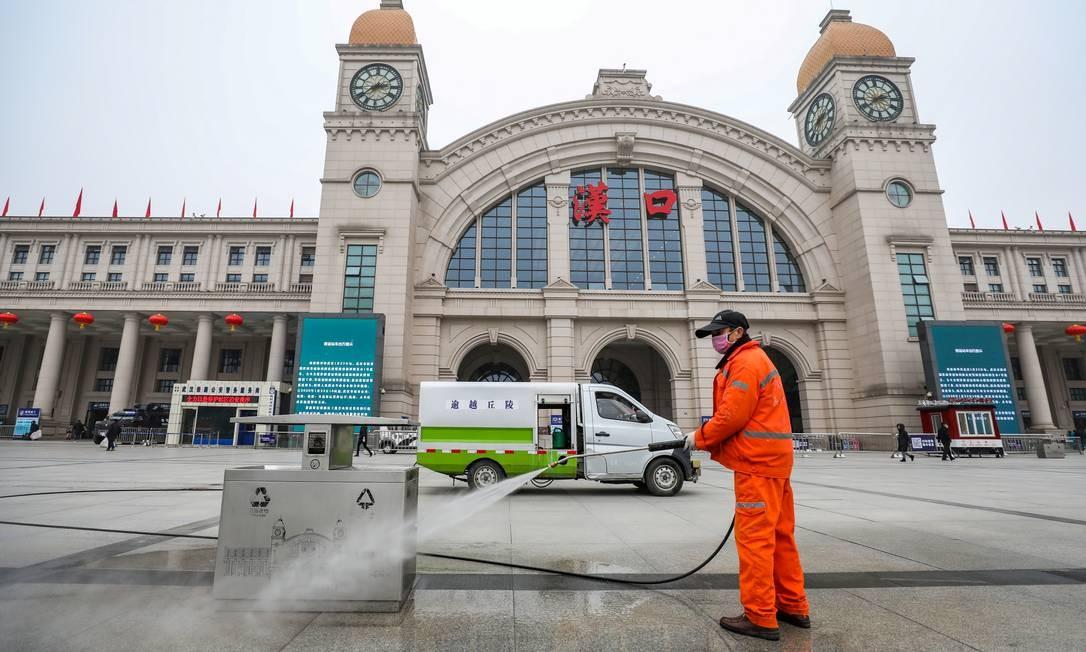 Agente faz trabalho sanitário em praça de Wuhan, na China. Foto: China Daily CDIC / Reuters