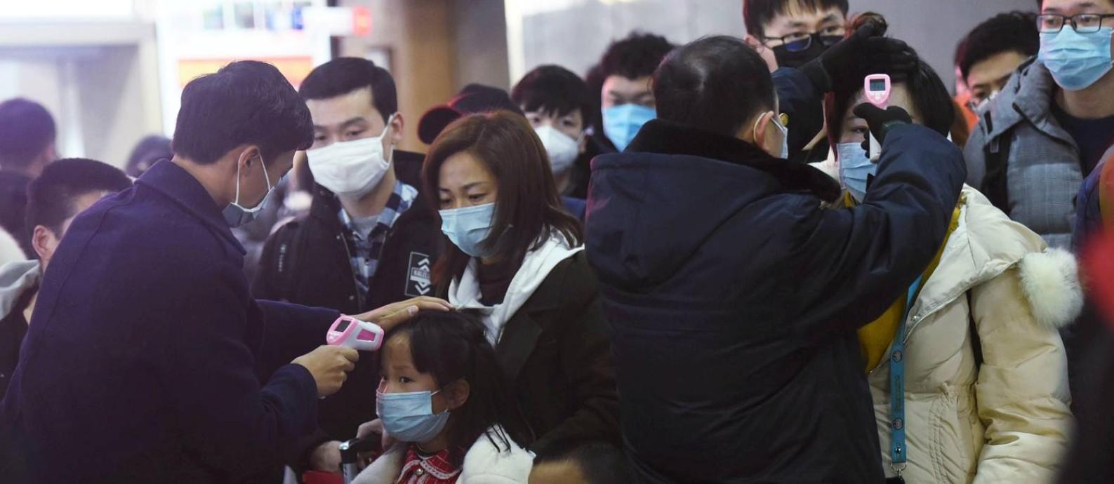 Funcionários checam temperatura corporal de passageiros que chegaram de Wuhan, epicentro da crise na China, na estaçaõ de trem de Hangzhou, na província de Zhejiang Foto: China Daily CDIC / REUTERS