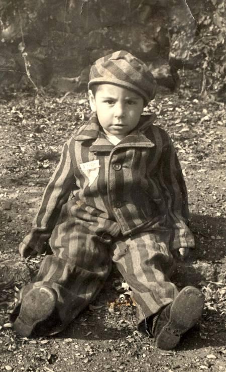 Um menino, vestindo uniforme de prisioneiro, fotografado logo após a libertação do campo de Auschwitz Foto: YAD VASHEM ARCHIVES / VIA REUTERS