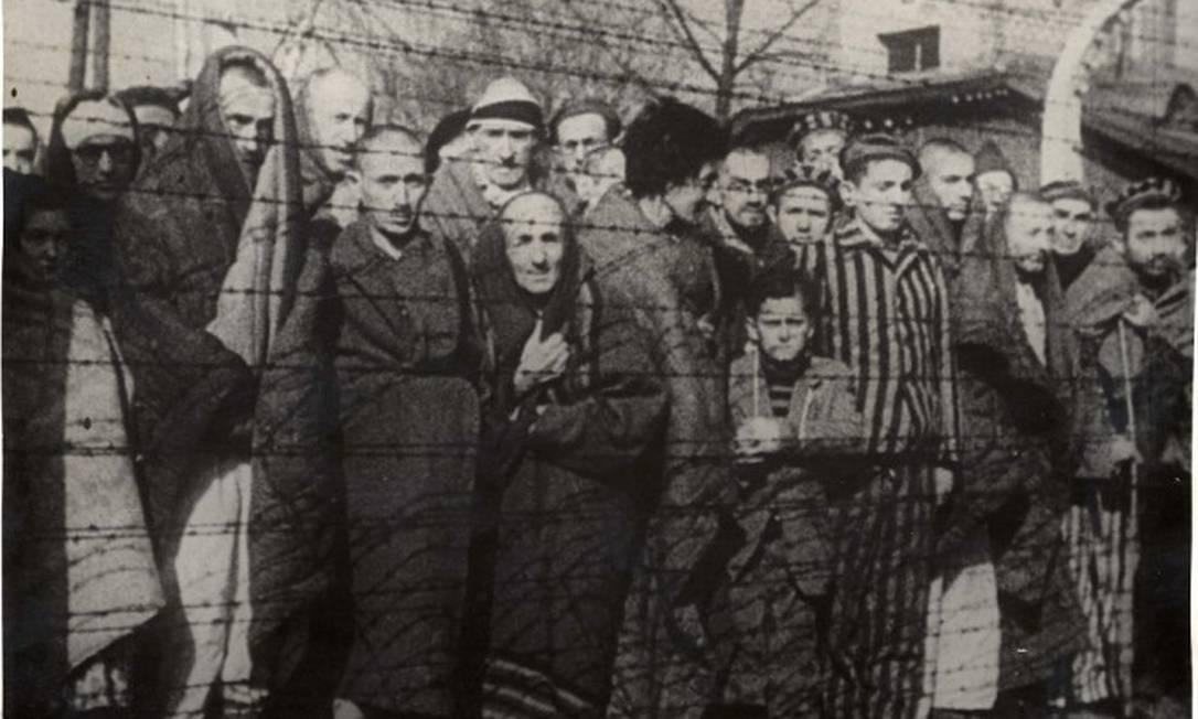 Sobreviventes do Holocausto atrás de cerca de arame farpado no dia da liberação de Auschwitz Foto: Yad Vashen Archives / Via Reuters
