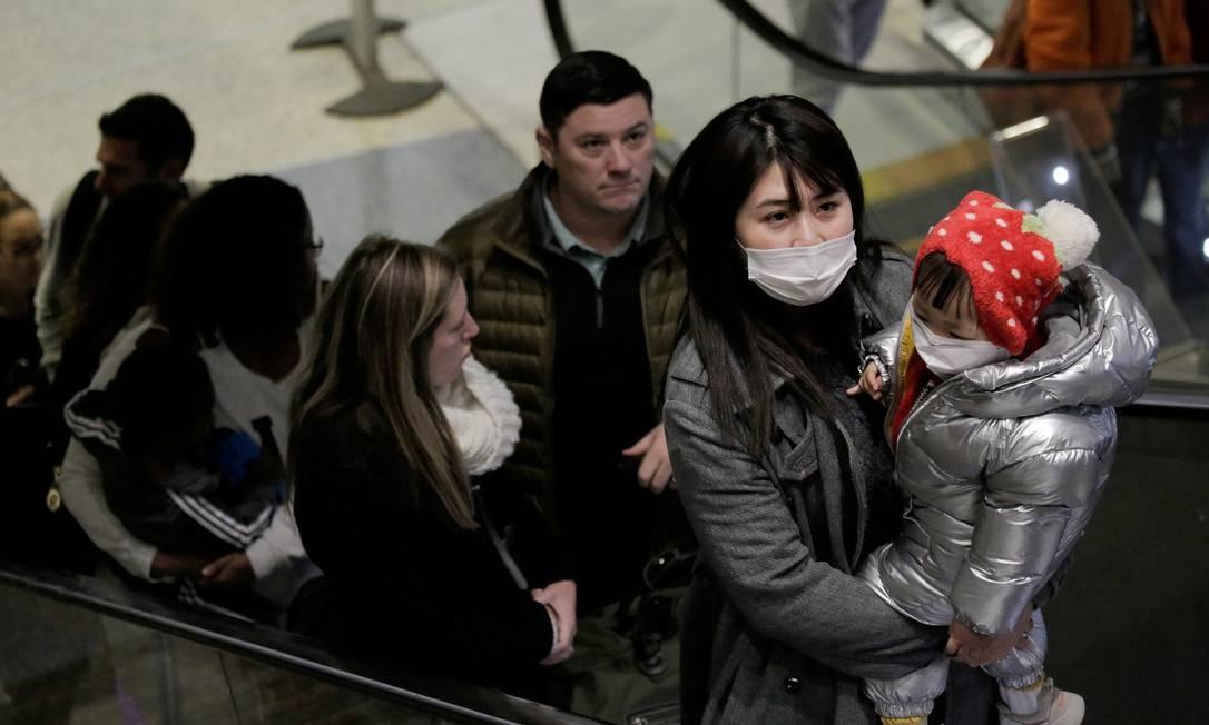 Viajantes usando máscaras chegam em voo direto da China, depois que porta-voz do Centro de Controle e Prevenção de Doenças dos EUA (CDC) disse que um viajante do país asiático foi a primeira pessoa nos Estados Unidos a ser diagnosticada com o coronavírus Foto: David Ryder / REUTERS