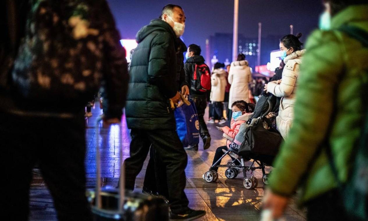 Pessoas usam máscaras protetoras na saída da estação ferroviária de Pequim Foto: NOEL CELIS / AFP