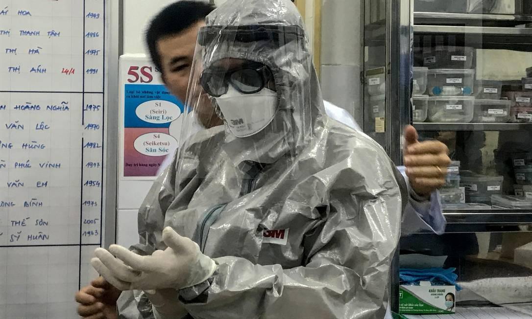 O vice-ministro da Saúde do Vietnã, Nguyen Truong Son, veste um traje de proteção antes de entrar em uma área de isolamento para visitar os dois primeiros casos da nova infecção por coronavírus, no hospital Cho Ray, na cidade de Ho Chi Minh Foto: BACH DUONG / AFP