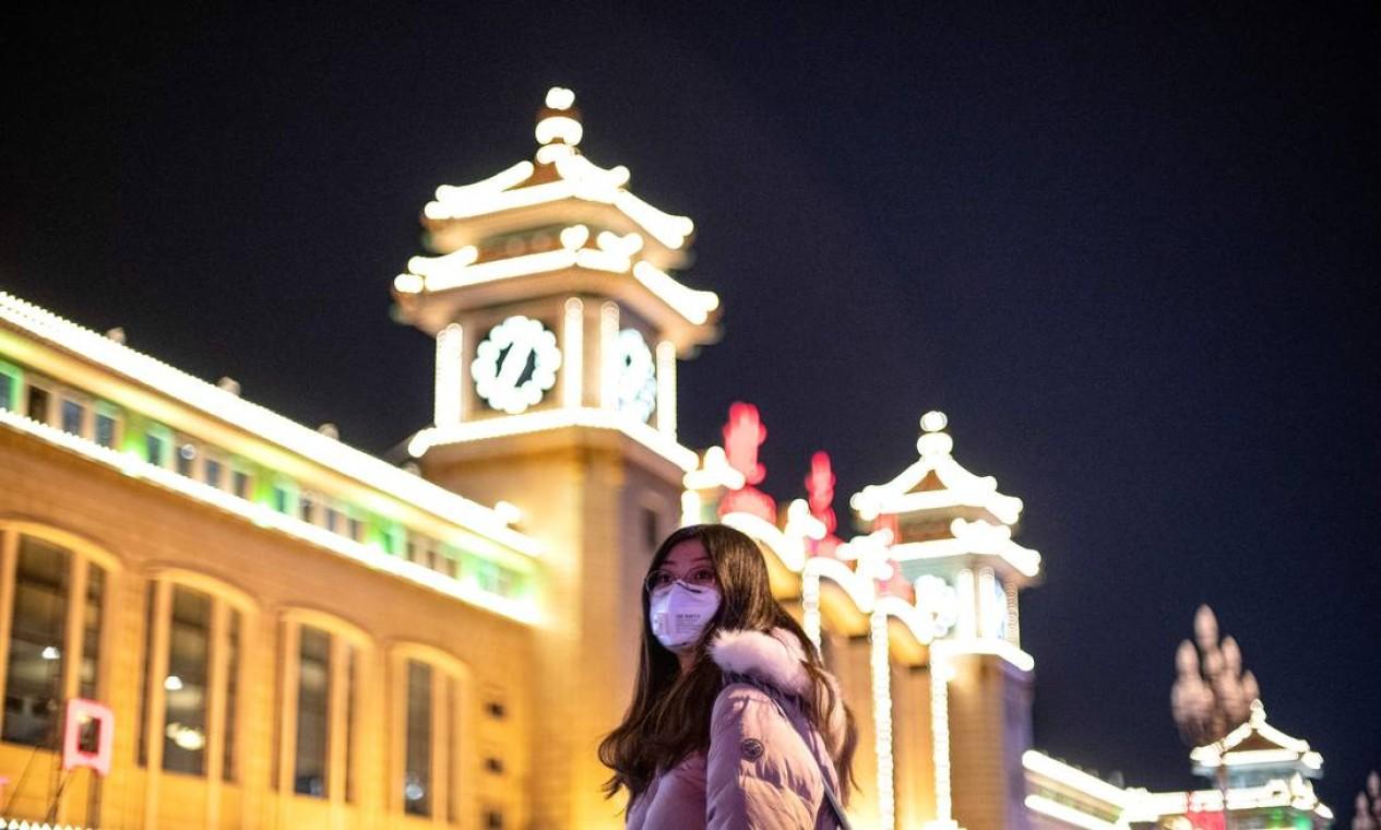 """Mulher usa máscara protetora do lado de fora da estação ferroviária de Pequim. A Organização Mundial da Saúde (OMS) declarou, na quinta-feira (23), que """"não é hora"""" de declarar o coronavírus como emergência global Foto: NOEL CELIS / AFP"""