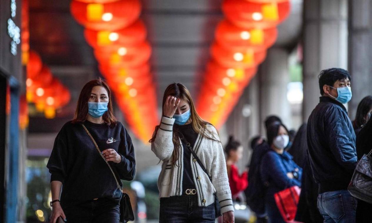 Pessoas usam máscaras faciais na saída do hotel New Orient Landmark, em Macau, depois que a ex-colônia portuguesa relatou seu primeiro caso de paciente diagnosticado com coronavírus Foto: ANTHONY WALLACE / AFP
