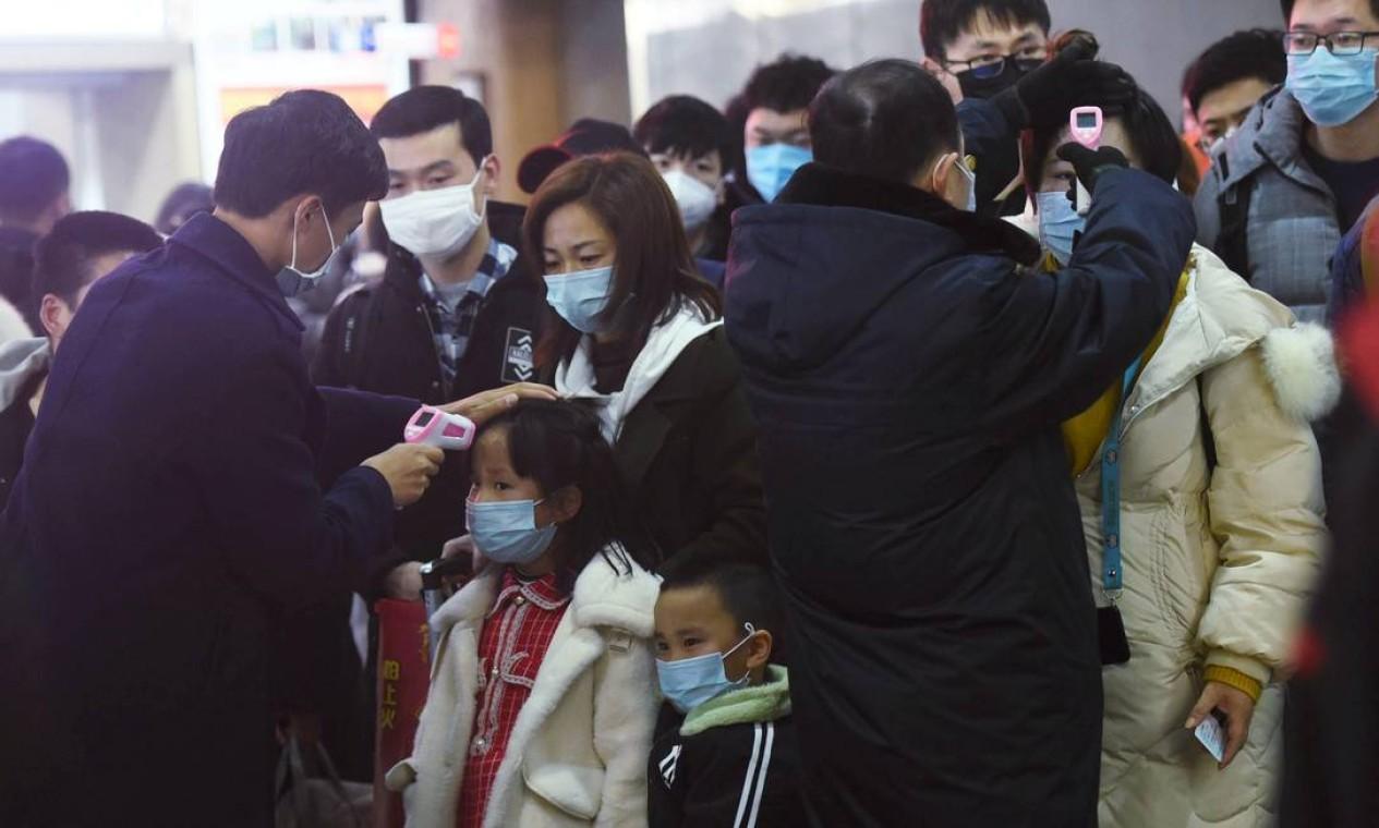 Funcionários verificam a temperatura corporal dos passageiros que chegam do trem de Wuhan para Hangzhou, na China Foto: CHINA DAILY / REUTERS