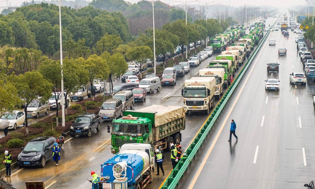 Foto aérea mostra engarrafamento de caminhões com material de construção, aguardando para abastecer canteiro de obras Foto: STR / AFP