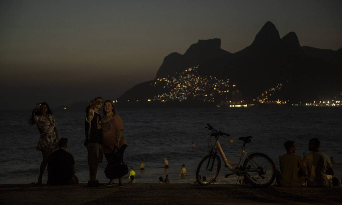 Cariocas e turistas cada vez mais aproveitma a praia como espaço de lazer depois que o sol se põe. Na foto pessoas desfrutam da paisagem do Arpoador à noite Foto: Agência O Globo/Guito Moreto