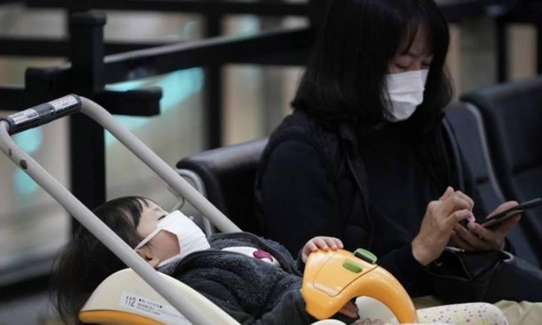 Mulher e criança com máscaras no aeroporto internacional de Tóquio; fábrica de máscaras está trabalhando extra para atender demanda Foto: EPA