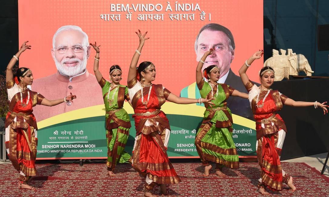 Dançarinas se apresentam em frente a cartaz de recepção ao presidente Jair Bolsonaro Foto: PRAKASH SINGH / AFP