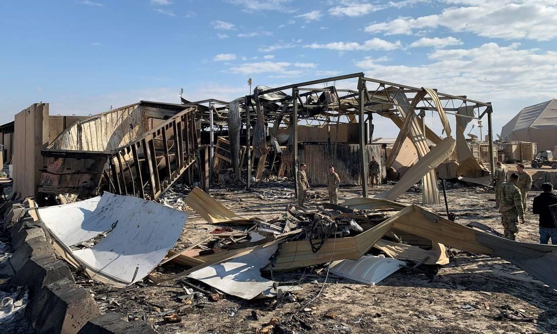 Soldados americanos vistos em meio aos destroços de um galpão da base iraquiana de Ain al-Asad, atingida por mísseis iranianos Foto: AYMAN HENNA / AFP/13-01-2020