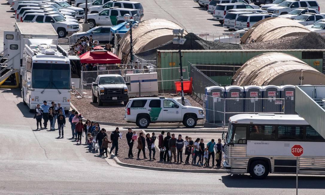 Imigrantes entram em ônibus no centro de detenção na fronteira entre o México e o estado americano do Texas Foto: PAUL RATJE / AFP